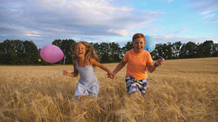 Couple of happy little kids with balloons in arms jogging through wheat field. Small girl and boy holding hands of each other and running among barley plantation. Concept of child love. Slow motion Imagens - 157508616