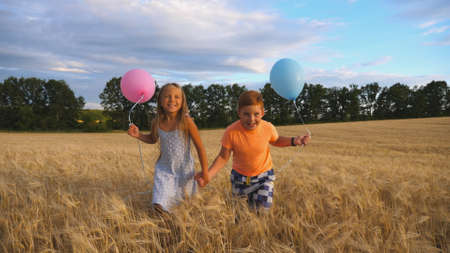 Couple of happy little kids with balloons in arms jogging through wheat field. Small girl and boy holding hands of each other and running among barley plantation. Concept of child love. Slow motion Imagens - 157508618