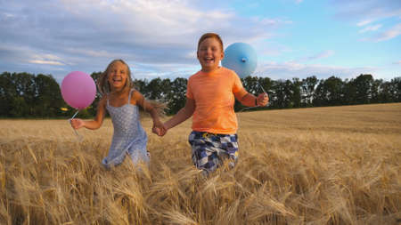 Couple of happy little kids with balloons in arms jogging through wheat field. Small girl and boy holding hands of each other and running among barley plantation. Concept of child love. Slow motion Imagens - 157508620