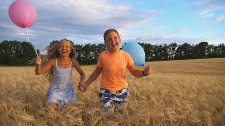 Couple of happy little kids with balloons in arms jogging through wheat field. Small girl and boy holding hands of each other and running among barley plantation. Concept of child love. Slow motion Imagens - 157508621