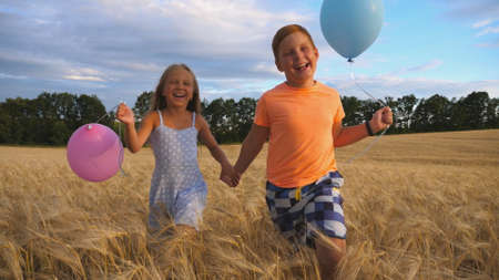 Couple of happy little kids with balloons in arms jogging through wheat field. Small girl and boy holding hands of each other and running among barley plantation. Concept of child love. Slow motion Imagens - 157510288