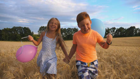 Couple of happy little kids with balloons in arms jogging through wheat field. Small girl and boy holding hands of each other and running among barley plantation. Concept of child love. Slow motion