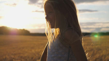 Close up of joyful smiling girl jumping against the blurred background of barley field at sunset. Happy laughing kid with blonde hair having fun at the wheat meadow with sunlight background.
