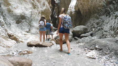 Group of young hikers walking across narrow canyon. Tourists strolling in rocky terrain and looking around enjoying scenic view. Travelers exploring gorge. Concept of travel or active rest. Slow mo