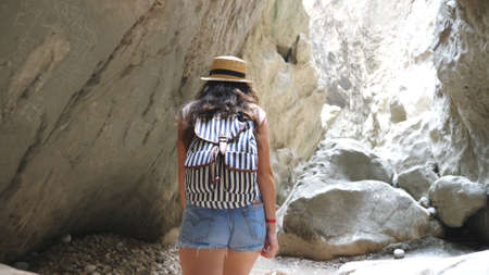 Unrecognizable woman with backpack walking across narrow canyon. Hiker in hat strolling in rocky terrain and looking around enjoying scenic view. Follow to female tourist exploring gorge. Slow motion Imagens - 157510295