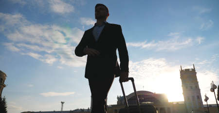 Businessman walking at urban environment with his luggage. Confident manager going to terminal with beautiful cityscape and sunset at background. Successful man going to home after flight. Slow motion Imagens