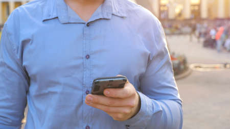Hand of businessman in shirt standing among city street and browsing smartphone. Confident man writing message or using app on his phone during break in work. Blurred background Imagens - 157510317