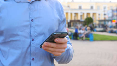 Successful businessman in shirt standing among city street and browsing smartphone. Confident man writing message or using app on his phone during break in work. Blurred background. Slow mo Close up. Imagens - 157510318
