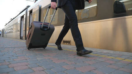 Legs of successful businessman in suit walking along platform and pulling suitcase on wheels. Feet of young confident man with his luggage strolling near train. Concept of business trip. Slow mo