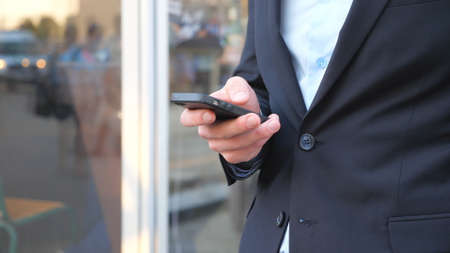 Successful businessman in suit standing among city street and browsing smartphone. Confident man typing text or using app on his phone during break in work. Blurred background. Slow motion Close up Imagens
