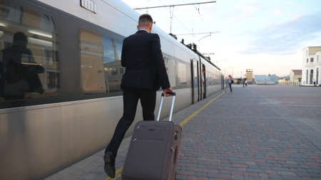 Unrecognizable successful businessman in suit running along platform and pulling suitcase on wheels. Young confident man with his luggage hurrying on train. Concept of business trip. Slow mo Back view Imagens - 157510333
