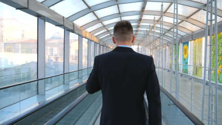 Confident businessman walking through glass hall of terminal with his luggage and talking on phone. Successful entrepreneur ending work conversation being on his way to flight. Slow motion Back view