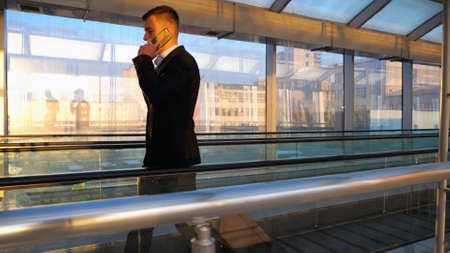 Confident businessman walking through glass hall of terminal with his luggage and talking on phone. Successful entrepreneur having work conversation being on his way to flight. Slow motion Side view Imagens - 157510338