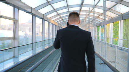 Confident businessman walking through glass hall of terminal with his luggage and talking on phone. Successful entrepreneur having work conversation being on his way to flight. Slow motion Back view Imagens
