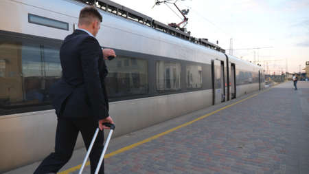 Unrecognizable successful businessman in suit running along platform and pulling suitcase on wheels. Young confident man with his luggage hurrying on train. Concept of business trip. Slow mo Back view