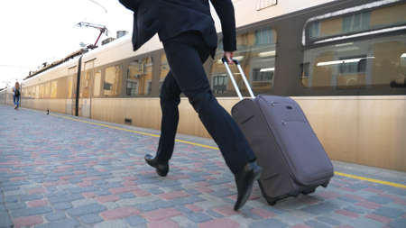 Legs of successful businessman in suit running along platform and pulling suitcase on wheels. Feet of young confident man with his luggage hurrying on train. Concept of business trip. Slow mo Close up Imagens - 157510344
