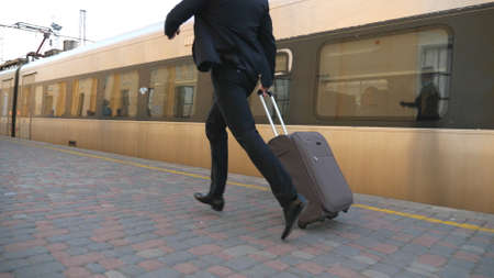 Legs of successful businessman in suit running along platform and pulling suitcase on wheels. Young confident man with his luggage missed train. Concept of business trip. Slow mo Side view Close up Imagens - 157510345