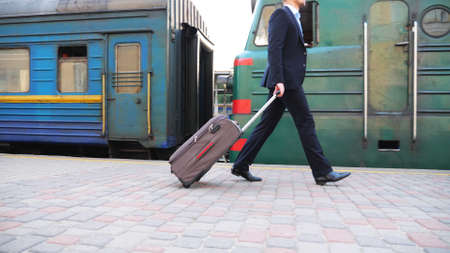 Unrecognizable successful businessman in black formal suit walking along platform near passing train. Young confident man with his luggage going on business trip. Stylish man stepping outdoor. Slow mo Imagens - 157510346