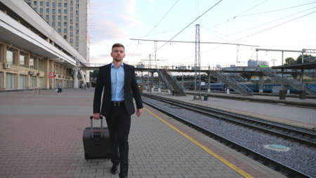 Portrait of successful businessman in black formal suit walking along platform with his luggage. Young confident man going on business trip. Stylish man stepping outdoor. Travel concept. Slow motion