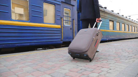 Unrecognizable successful businessman in black formal suit walking along platform and pulling suitcase on wheels. Young confident man with his luggage strolling near passing train. Slow mo Back view Imagens