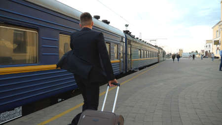 Unrecognizable successful businessman in black formal suit running along platform late for train. Young confident man with his luggage hurrying to business trip. Travel concept. Slow motion Back view