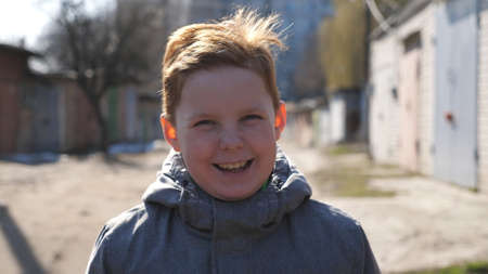 Happy joyful red-haired boy looking into camera and laughing outdoor. Portrait of small male ginger child with freckles outside. Close up positive emotions of little smiling kid on his face