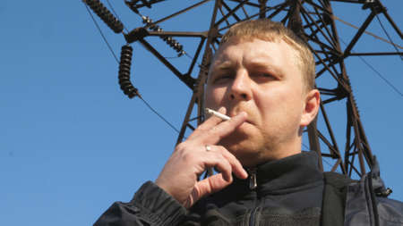 Portrait of adult serious man looking into camera and smoking cigarette outdoor. Concept of unhealthy habit and addiction. Blue sky at background. Low view Close up Slow motion