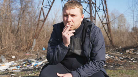 Adult serious man sits squatting and smoking cigarette outdoor. Male person looking into camera and throwing out a cigarette butt. Concept of unhealthy habit and addiction. Close up Slow motion