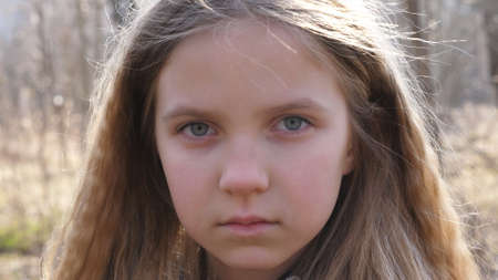 Little serious girl looking into camera outdoor. Close up emotions of female kid with unhappy expression on face. Portrait of upset child against the blurred background of a forest in early spring Imagens