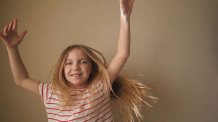 Happy smiling blonde girl dancing funny against the background of wall. Cheerful small female kid enjoying and having fun at home. Little child making dance movements indoor. Close up Slow motion