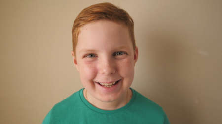 Happy joyful red-haired boy looking into camera and laughing indoor. Close up emotions of little smiling kid with glad expression on his face. Portrait of small male ginger child with freckles inside
