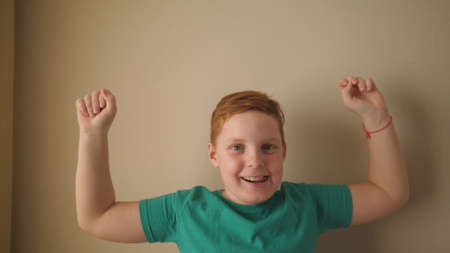 Happy male ginger child with freckles looking into camera and raises hands rejoicing achievement inside. Portrait of little red-haired boy with positive emotions on his face indoor. Slow motion