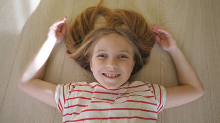 Little funny kid lying on the floor and looking into camera at room. Happy smiling blonde girl relaxing at home. Close up positive emotions of cute child on her face. Top view Slow motion