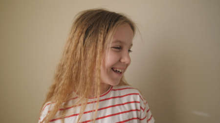 Little smiling female child looking to the side and laughing with someone indoor. Positive emotions of cute kid on her face. Happy small blonde girl against the background of wall. Close up Slow mo
