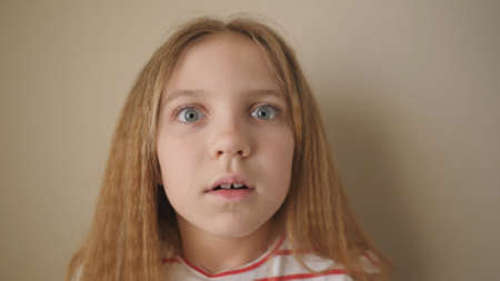 Little child with long blonde hair looking into camera with shocked expression inside. Portrait of beautiful girl showing fright indoor. Close up scared female face of small kid. Slow motion