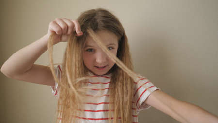 Close up of beautiful small girl weaving small pigtail out of her long blonde hair indoor. Little cute female child doing herself a hairstyle at home. Slow motion