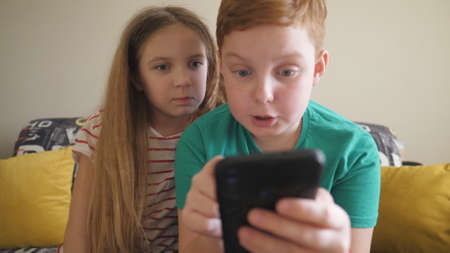Small children watch some interesting video on smartphone sitting on the sofa at room. Sister and brother looking a movie on mobile phone at home. Little boy and girl spending time together. Close up Imagens
