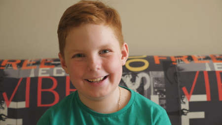Portrait of happy joyful red-haired boy sitting on the couch and looking into camera. Small male ginger child with freckles laughing indoor. Male face of little smiling kid with positive emotions