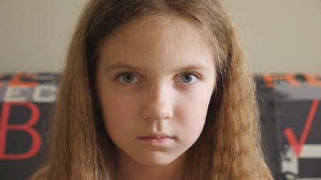Small disappointed kid sitting on the couch and looking into camera. Portrait of unhappy little girl with blonde hair indoor. Close up emotions of female child with sorrowful expression on her face Imagens