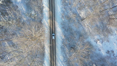 Aerial shot of white car start riding through snow covered icy road. SUV driving at countryside route in the forest on winter day. Flying over the auto moving through scenic landscape way. Top view Imagens
