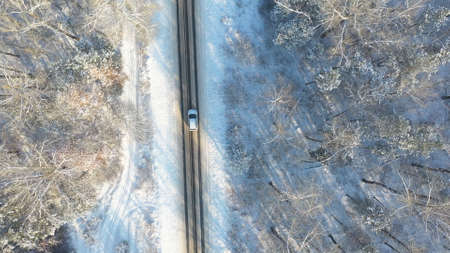 Aerial shot of white car riding through snow covered icy road. SUV driving at empty countryside route in the forest on winter day. Flying over the auto moving through scenic landscape way. Top view