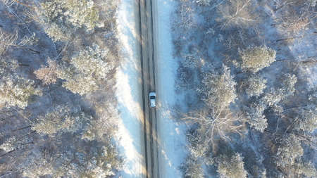 SUV driving at beautiful countryside route in the forest on winter day. Aerial shot of white car ride through snow covered icy road. Flying over the auto moving through scenic landscape way. Top view Imagens - 163735258