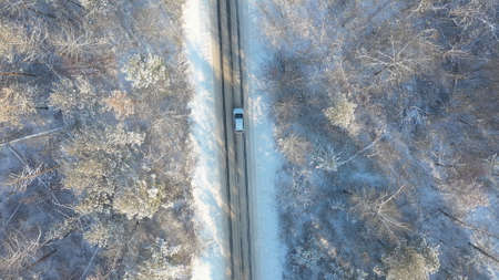 SUV driving at beautiful countryside route in the forest on winter day. Aerial shot of white car ride through snow covered icy road. Flying over the auto moving through scenic landscape way. Top view