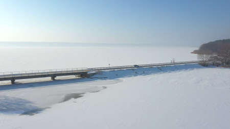 Aerial shot of white car riding through snow covered road near a frozen lake. SUV driving at countryside route near icy pond at sunny winter day. Flying over the auto moving through scenic landscape