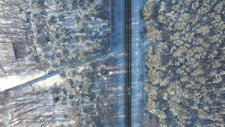 White car riding through snowy rural road. Following to SUV driving at beautiful countryside route on wintry day. Winter holidays journey at nature. Concept of family travel. Aerial shot Top View Imagens