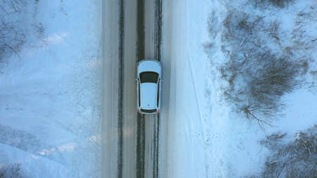 Close up of white car riding through snowy forest road. SUV driving at beautiful countryside route on wintry day. Winter holidays journey at nature. Concept of family travel. Aerial shot Top View Imagens