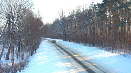 White car fast riding through snow covered icy road. SUV going at empty countryside route in winter forest on sunny day. Auto moving through scenic landscape way. Travel concept Top view Drone shot