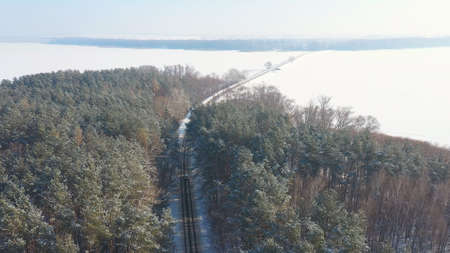 Aerial shot of white SUV going on a snow covered forest road. Car rides at icy woods route at winter time. Auto driving over beautiful nature way. Concept of travel and active weekends. Above view