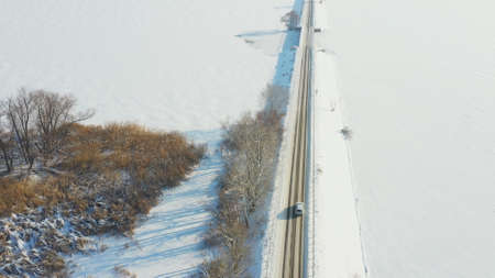 Aerial shot of car riding through snow covered road near frozen lake. White SUV driving at dam route on winter day. Flying over the auto moving through bridge of river. Scenic landscape way. Top view Imagens - 163735413
