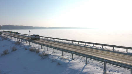 Aerial view of car riding through snow covered road near frozen lake. White SUV driving at dam route on winter day. Fly over the auto moving through bridge of river. Scenic landscape way. Drone shot Imagens